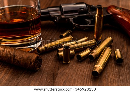 Empty shells from the weapons with glass of whiskey and revolver with cuban cigar on a wooden table - stock photo