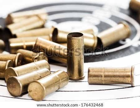 empty shells of small-bore rifle on paper target for shooting practice - stock photo