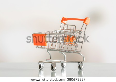 Empty shopping cart in orange color in a market