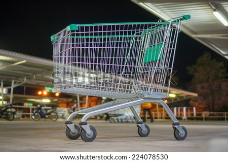 Empty shopping cart with green handle on parking near supermarket in evening - stock photo