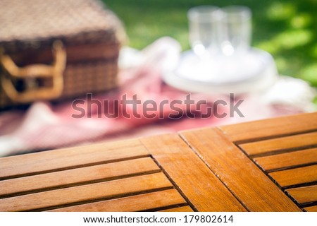 Empty slatted wooden picnic table for your product placement with a blurred wicker picnic hamper and rug with glasses and plates on a green lawn behind - stock photo