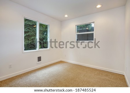 Empty small room with two windows, white walls and beige carpet floor