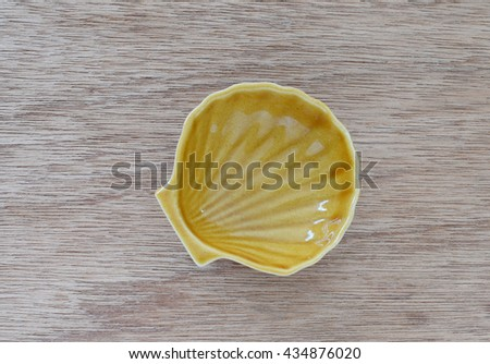 Empty small shell-shaped plate on wood background - stock photo