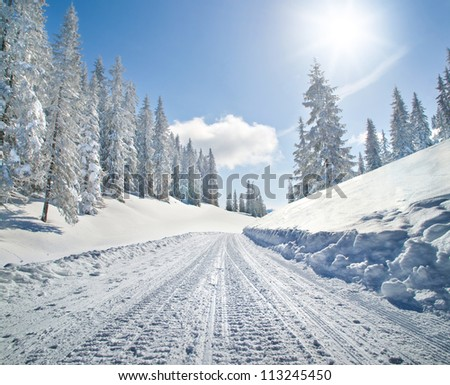 Empty snow covered road in winter landscape - stock photo