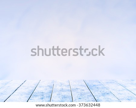 empty snow wooden deck table top Ready for product display montage with  snow  background in the winter.  - stock photo