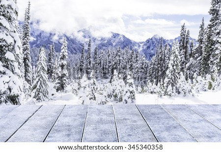 empty snow wooden deck table top Ready for product display montage with snow forest background in the winter. - stock photo