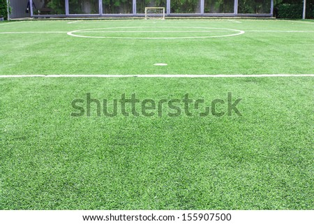 Empty soccer field with goal with green plastic glasses - stock photo