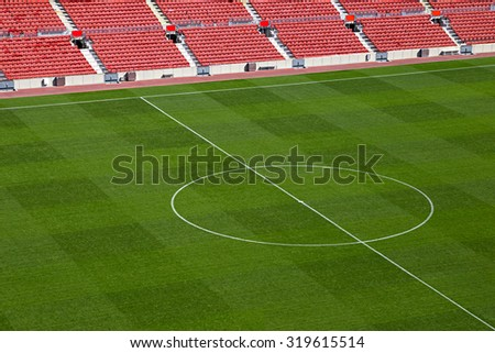 empty soccer stadium with red seat shells and green field