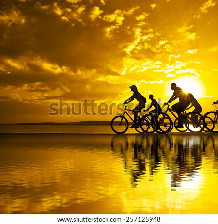 Empty Space for inscription Sporty company friends on bicycles outdoors sunset Silhouette five 5 cyclist going along shoreline coast Reflection sun on water Sport in Nature background Group of people - stock photo