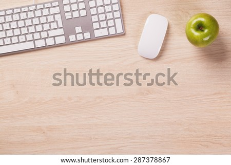 Empty space next to office equipment such as computer modern keyboard, white mouse and green apple on bright wooden office desk.