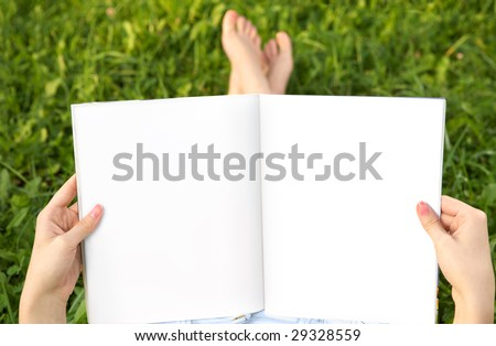 Empty spread in female hands against feet and a summer meadow - stock photo