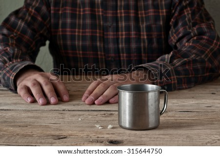 Empty steel cup bread crumbs on a wooden table closeup. In the background male hand. Free space for text. Copy space. - stock photo