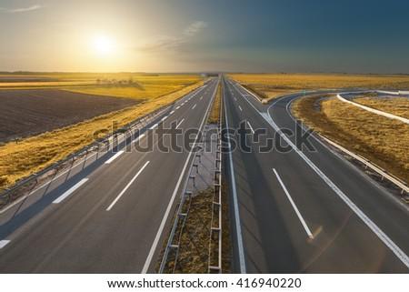 Empty, straight highway towards the sun at beautiful autumn sunset near Belgrade, Serbia. - stock photo