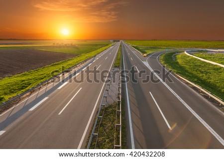 Empty, straight highway towards the sun at beautiful spring sunset near Belgrade, Serbia. - stock photo