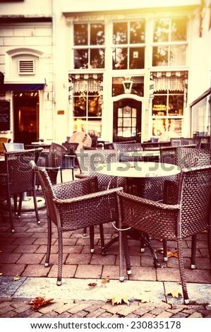 Empty street cafe terrace in autumn city - stock photo