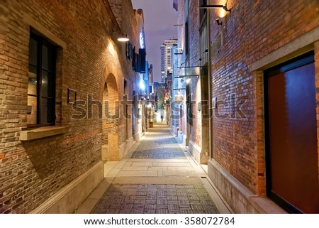 Empty street in the nigh with brick walls and warm light
