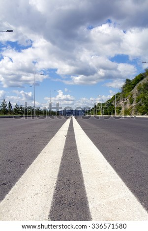 Empty street to big city. Blue sky and white clouds. Vertical composition - stock photo