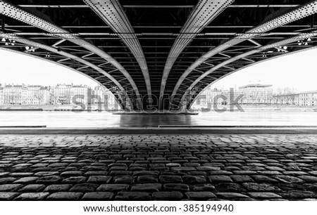 Empty street under a bridge crossing the Rhone river in Lyon on a cold winter day. - stock photo