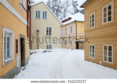 Empty street with old houses with fresh snow all around