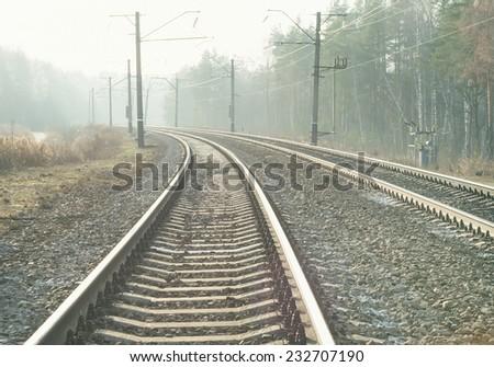 Empty suburban railroad leading to the horizon on a sunny clear day - stock photo