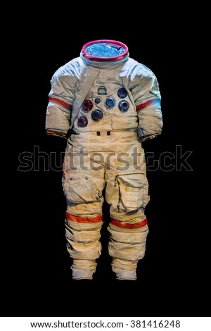 Empty suit of an astronaut on a black background. Old protective space suit for cosmonaut. Used spacesuit on dark background.  - stock photo
