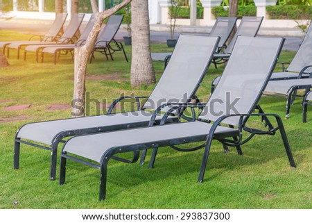 Empty sunbeds on park at tropical beach. - stock photo