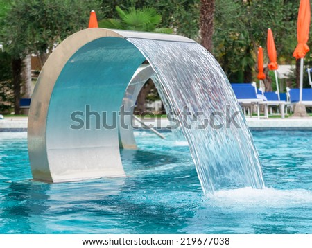 Empty Swimming pool in spa with waterfall jet - stock photo