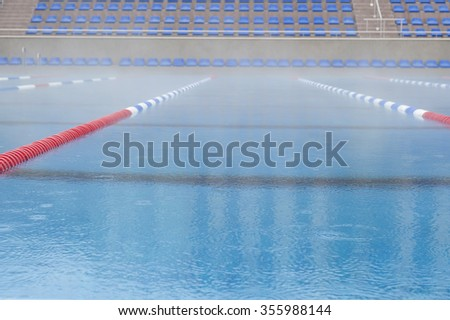 empty swimming pool with blue benches - stock photo