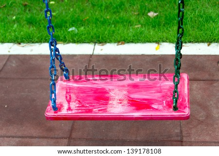 Empty swing set on red floor background - stock photo