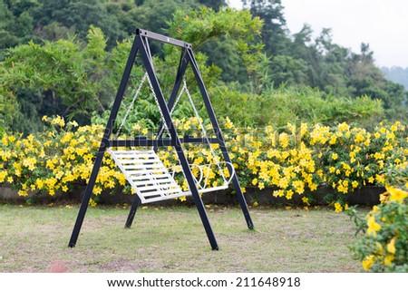 Empty swings in garden - stock photo