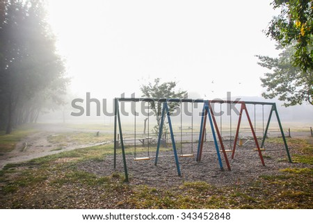 Empty swings on children playground in the mist