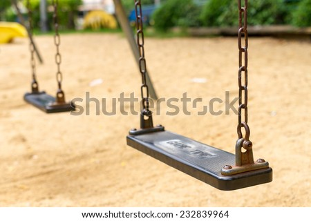 Empty swings on playground (selective focus)  - stock photo