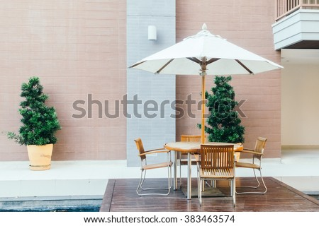 Empty Table and chair with umbrella on patio in the garden - Vintage Light Filter - stock photo