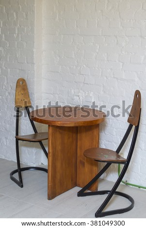 Empty table and chairs near him.
