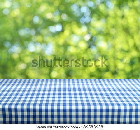 Empty table and defocused fresh green background - stock photo