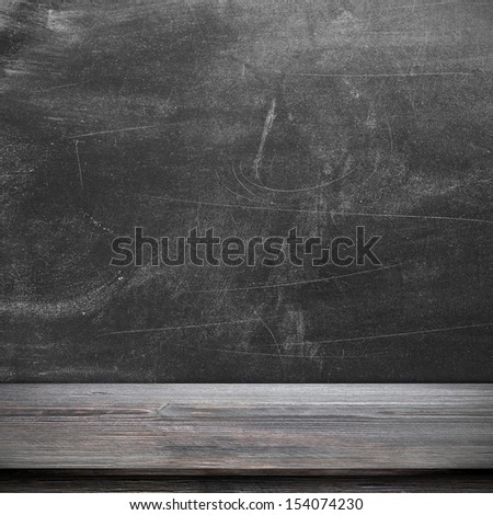 Empty table in class with blackboard - stock photo