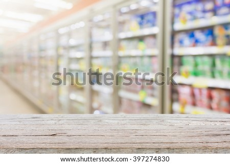 Empty table with blur supermarket refrigeratorr background - stock photo