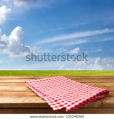 Empty table with tablecloth over beautiful meadow and blue sky - stock photo