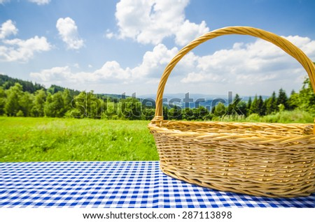 Empty table with wicker basket and landscape background - stock photo