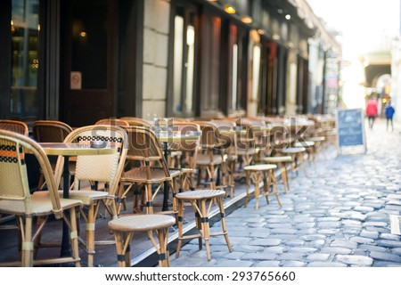 Empty tables in between dining hours along a Paris cobblestone alley - stock photo