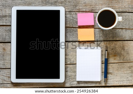 Empty tablet pc and coffee. Empty tablet, notebook, pen and a coffee on wood table - stock photo