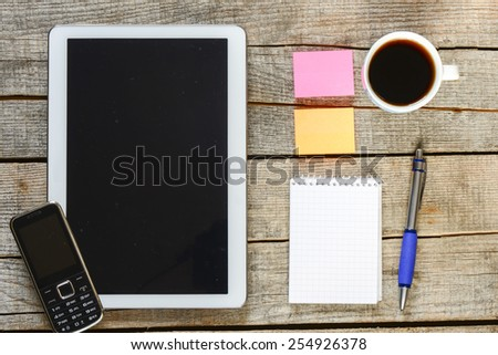 Empty tablet pc and coffee. Empty tablet pc,phone, notebook, pen and a coffee on wood table - stock photo