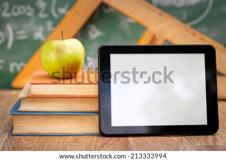 Empty tablet pc with books, technology and education  - stock photo
