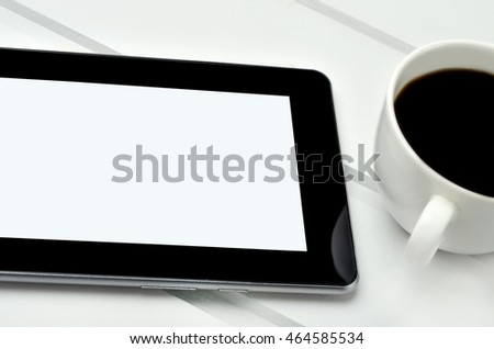 Empty tablet with coffee cup on wooden table