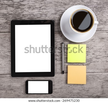 empty tablet with note paper and coffee on the wooden table - stock photo
