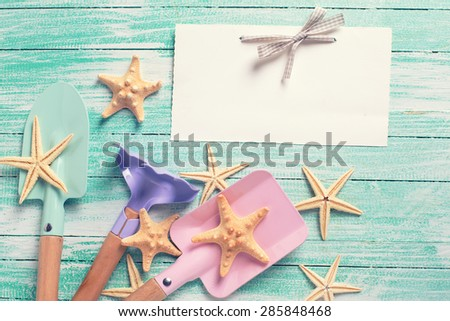 Empty tag and tools for children for playing in sand, sea object on turquoise  painted wooden planks. Place for text. Vacation, holiday, summer background.Toned image. - stock photo
