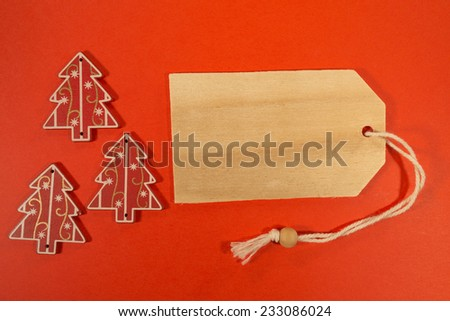 Empty tag with three Christmas decorations on red background. Three Christmas decoration with price tag - stock photo