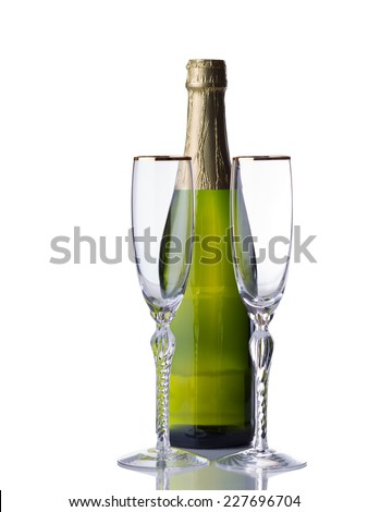 Empty tall elegant drinking glasses with unopened bottle of sparkling wine isolated over white background with reflection