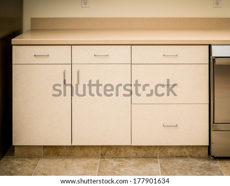 Empty tan kitchen counter and cabinet minimalist style - stock photo