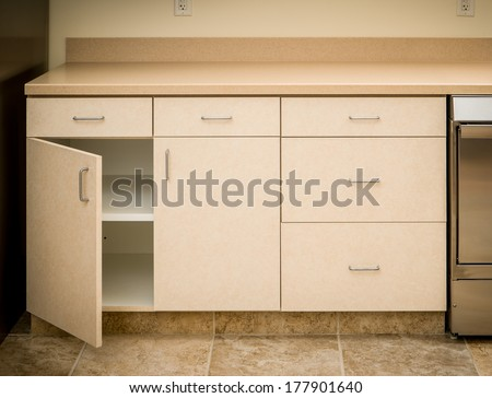 Empty tan kitchen counter and cabinet minimalist style with cabinet door open empty inside - stock photo
